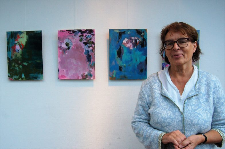 Regine Schirmer vor abstrakten Acrylarbeiten