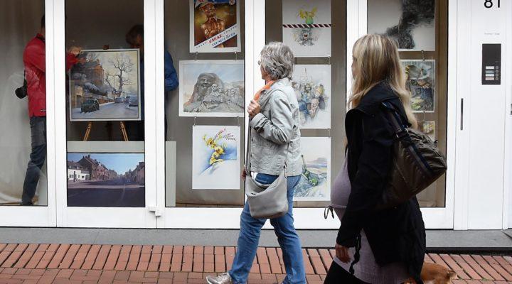 Im Vorbeigehen verfolgen Passanten, wie Horst Thelen (l.) und Peter Klaucke Bilder im Schaufenstern des Lades auf der Hauptstraße 81 aufhängen.