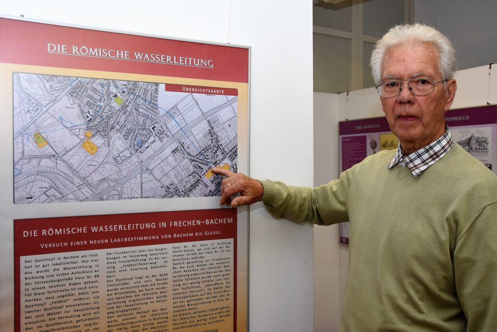 Josef Bucco zeigt auf die Sparkasse in Hürth-Gleuel, in der ein Stück römische Wasserleitung zu sehen ist.