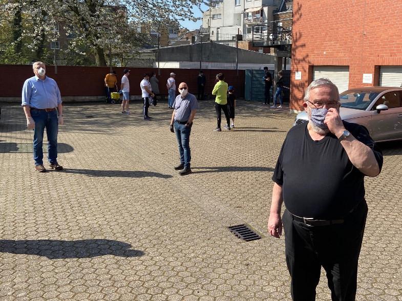 Helfer der Tafel Frechen bei der Einweisung auf dem Parkplatz am Pfarrheim St. Audomar