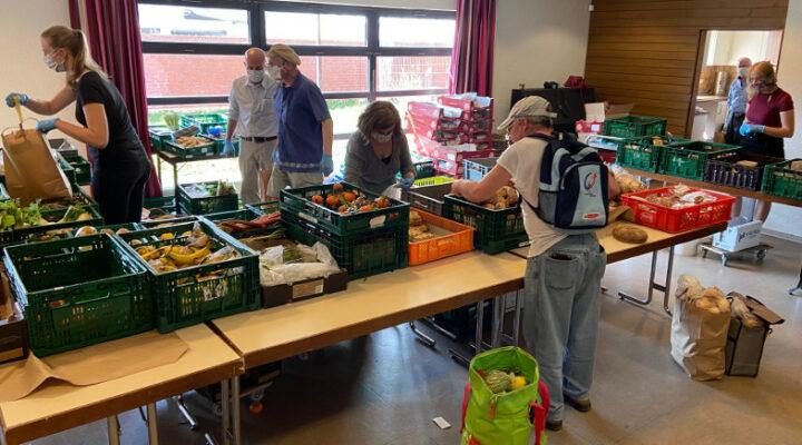 Kundin und Mitarbeitenden der Tafel Frechen bei der Lebensmittelausgabe im Pfarrheim St. Audomar